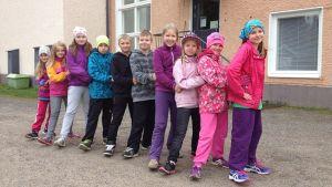 Joukko Kontiomäen koulun oppilaita on ryhmittynyt letkajenkkaan koulun pihalla.