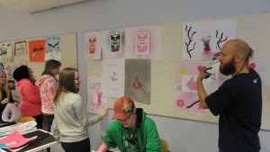 Kielikaara-työpajan ohjaaja Tony Fredriksson ja Ylitornion lukion ekaluokkalaisia ripustamassa työpajassa tehtyjä teoksia luokan seinälle.