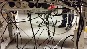 Sähkölaitteiden johtoja toimitsopöydän alla.