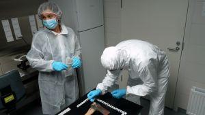 Suojapukuihin sonnustautuneet tutkijat tarkastelevat kirvestä jossa on punaisia verijälkiä