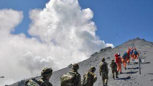 pelastajajoukko kiipeää jonossa vuorelle