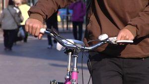 Pyöräilijä taluttaa polkupyörää Helsingissä.