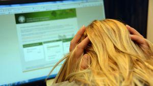 Kuvassa nainen tietokoneella.