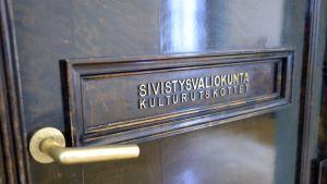 Sivistysvaliokunta-kyltti ovessa.