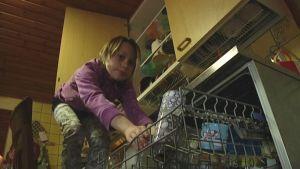 Tyttö tyhjentää astianpesukonetta.