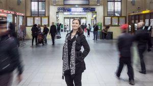 Eva Lönnblad seisoo Helsingin rautatieasemalla ihmisten keskellä