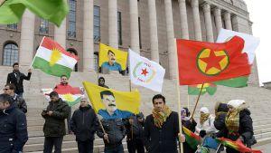 Joukko Suomessa asuvia kurdeja osoitti mieltään Isisin saartaman Kobanen kaupungin tueksi eduskuntatalon edessä tiistaina.