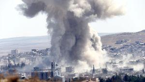 Räjähdyksen nostattama savupilvi nousee rakennusten keskeltä.