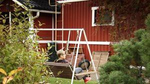 Pirjo Keto keinuu talonsa pihassa.