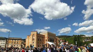Ihmiset kerääntyivät sodassa tuhotun ja sittemmin remontoidun kaupungintalon edustalle Sarajevossa 9. toukokuuta 2014.
