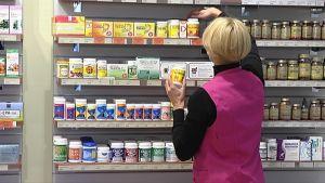 Myyjä asettelee vitamiinipurkkeja hyllyyn.