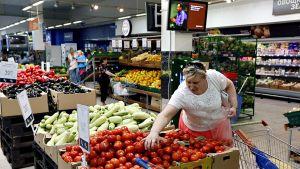 Asiakas valitsee tomaatteja moskovalaisessa supermarketissa 7. elokuuta.