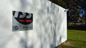 ISS-vartiointiliikkeen logo ja toimimaton turvakamera taidekolmion seinässä.