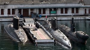 Kolme sukellusvenettä laiturissa satamassa.