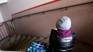 Nuori istuu yksin portaikossa.