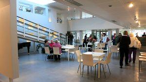 Ihmisiä istuu taidemuseon aulakahviossa.
