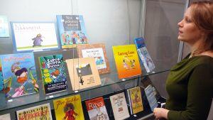 Minttu Tervaharju katselee vitriinissä olevia lastenkirjoja.