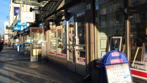Kauppakadulla osassa liikkeistä ovi on kiinni ja osassa auki.