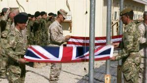 Sotilaat käärivät Iso-Britannian ja Yhdysvaltojen lippuja.