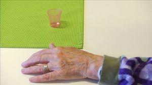 Vanhuksen käsi ja lääkekuppi pöydällä.