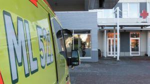Ambulanssin kylki, ambulanssi seisoo Länsi-Pohjan keskussairaalan päivystysvastaanoton pihalla.
