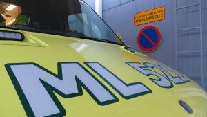 Ambulanssin keula, taustalla näkyy liikennemerkki Pysäköinti sallittu vain ambulansseille.