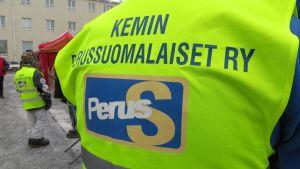 """Markkinavalvojan liivi, jonka selässä teksti """"Kemin perussuomalaiset ry""""."""