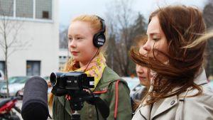 Tytöt kuvaavat uutisjuttua videokameralla.