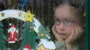 Lapsi katsoo sateisen ikkunan lävitse.