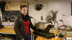 Eläintentäyttäjä Sari Mastromarino seisoo täyttämänsä mäyrän vieressä.