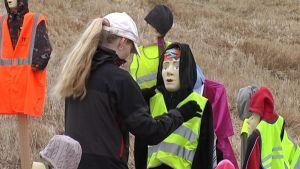 Päivi Kauhanen korjaa Porintien varressa seisovaa koululaishahmoa.