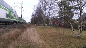 Juna kulkee läheltä asutusta.
