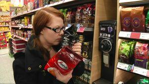 Kuvassa nainen haistelee kahveja kaupassa