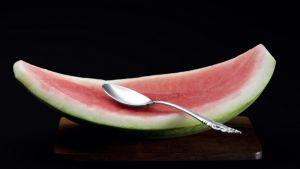 Syöty vesimeloni ja tyhkä lusikka pöydällä