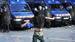 Mielenosoittaja näyttää sukuelimiään poliiseille.