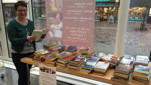 Kirjastotoimenjohtaja Susan Forsberg esittelee Nenäpäivä-viikoksi katettua kirjatoria, jonne ihmiset ovat lahjoittaneet opuksiaan myytäväksi hyvään tarkoitukseen.