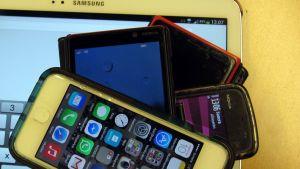 kuvassa tabletti ja kännyköitä päällekkäin