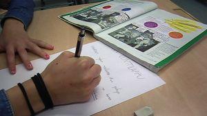 Oppilas tekee koetta pulpetissa.