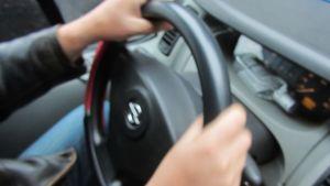 Rattijuoppo - hieman sumea kuva autonratista. Viinapullo ratin edessä.