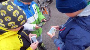 Lapsia pelaamassa älypuhelimilla