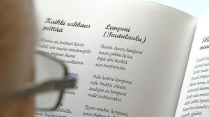 Kuvassa lihminen selaa kirjaa, josta näkyy tekstiä.