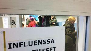 Influenssarokotteenottajia Kajaanin pääterveysasemalla.