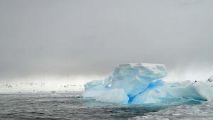 Kumivene ja jäävuori Graham Passagessa Etelämantereella.