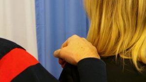 Miehen käsi naisen olkapäällä