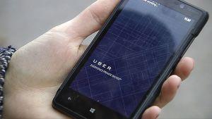 Naisella on kädessään älypuhelin, jossa on UBERin sovellus.