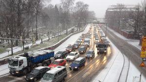 Lunta sataa Helsingissä, autot seisovat ruuhkassa