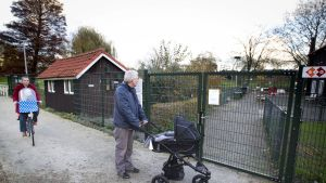 Mies seisoi lastenvaunujen kanssa suljetun kotieläintarhan portilla Waddinxveenin kaupungissa, Hollannissa 17. marraskuuta 2014. Kaikki Hollannin kotieläintarhat on jouduttu sulkemaan H5N1-tyypin lintuinfluenssan vuoksi.