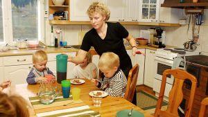 Perhe ruokailee keittiössä.