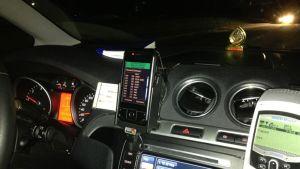 Auto ajaa pimeällä tiellä taksia vastaan.