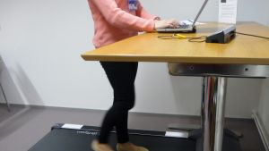 Nainen kävelee kävelymatolla toimistopöydän edessä.
